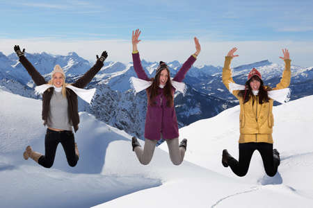 Happy young women jumping in winter in the mountains in the snow photo