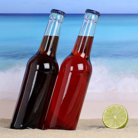 soft drinks: Cola and lemonade soft drinks on the beach in sand and sea Stock Photo