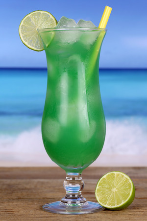 longdrink: Lime fruit cocktail on the beach while on vacation