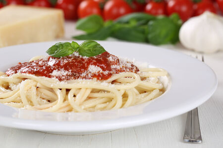 Cooking spaghetti noodles pasta: prepared meal with tomato sauce and basil on plate photo
