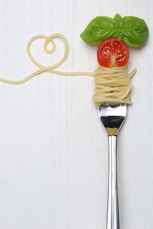 pasta: Fideos espaguetis comida de pasta con el coraz�n, el tomate y el espacio de la copia en un tenedor