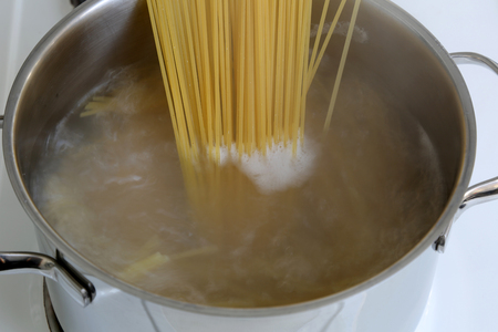 Preparing spaghetti pasta meal: cooking noodles in water in pot