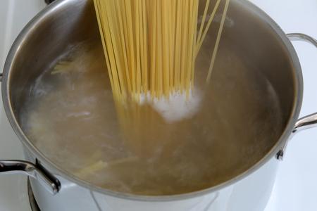 Voorbereiding van spaghetti pasta maaltijd: koken noedels in water in pot Stockfoto