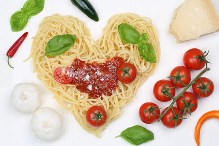 Ingredients spaghetti noodles pasta with heart on wooden board photo