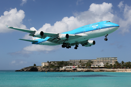 plane landing: St. Martin - February 9, 2014: A KLM Royal Dutch Airlines Boeing 747-400 with the registration PH-BFY approaching St. Martin Airport (SXM). St. Martin is rated one of the most dangerous airports in the world. Editorial