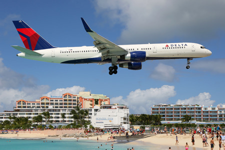 airplane landing: St. Martin - February 8, 2014: A Delta Airlines Boeing 757-200 with the registration N6714Q approaching St. Martin Airport (SXM). St. Martin is rated one of the most dangerous airports in the world. Delta Air Lines is the worlds largest airline with 733  Editorial