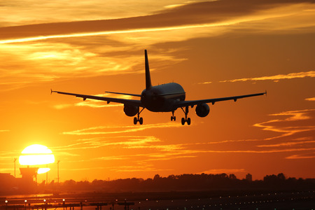 An airplane landing at an airport during sunset on vacation during a journey Stock Photo
