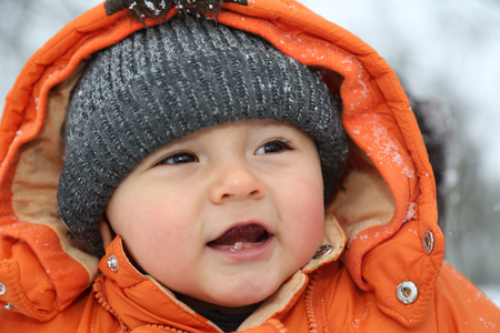 Portrait of a smiling baby boy with snow in winter with cap and winter clothes Stock Photo