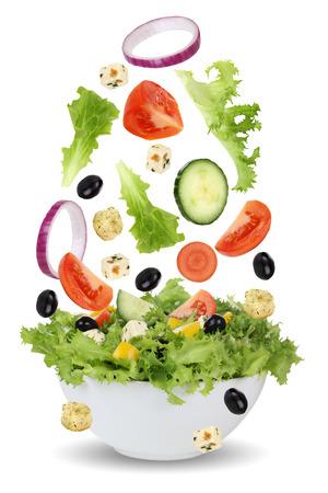 Dalende salade in kom met sla, tomaten, Feta kaas, Ui, Olijven en Komkommer Stockfoto