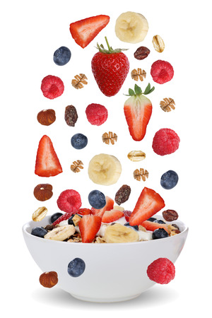 Falling ingredients of fruit muesli for breakfast in bowl with fruits like raspberry, blueberries, banana and strawberry