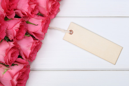 valentine's day: Roses flowers on Valentines or mothers day with empty greeting card and copyspace on a wooden board