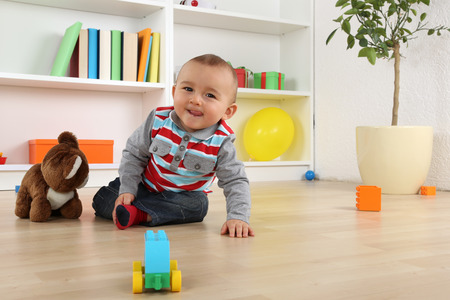 Portrait of a smiling baby child playing with toys in childrens room