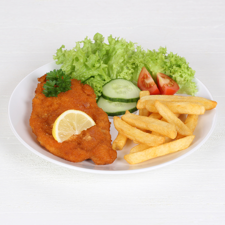 schnitzel: Schnitzel with french fries, vegetables, lemon and salad on plate