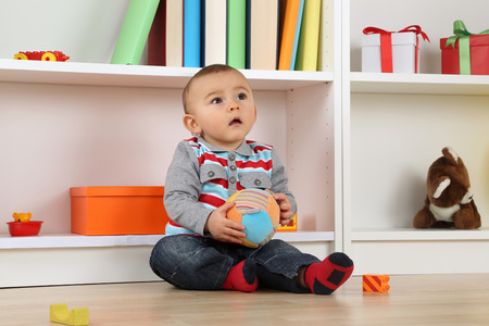 childrens playing: Baby child playing with ball and looking up in childrens room