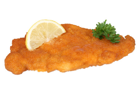 Schnitzel chop cutlet with lemon and parsley isolated on a white background