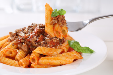 bolognaise: Eating Penne Rigate Bolognese or Bolognaise sauce noodles pasta meal on a plate