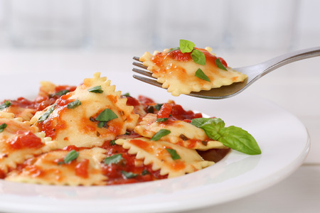 Eating Ravioli with tomato sauce meal with basil on a plate