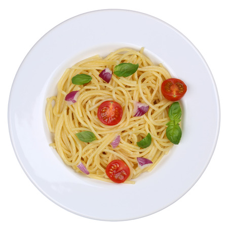 dinner plate: Spaghetti noodles pasta meal with tomatoes and basil on plate isolated from above Stock Photo