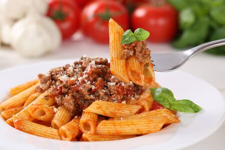 penne: Eating pasta Bolognese or Bolognaise sauce noodles meal on a plate Stock Photo