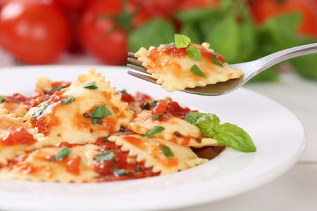 pasta: Eating Italian Pasta Ravioli with tomato sauce noodles meal with basil on a plate