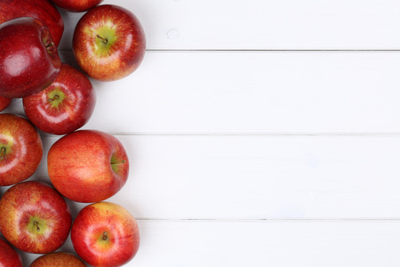 Red apple fruits background on a wooden board with copyspace