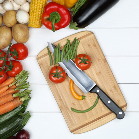 knife tomato: Vegetarian and vegan eating smiling face from vegetables on cutting board with knife