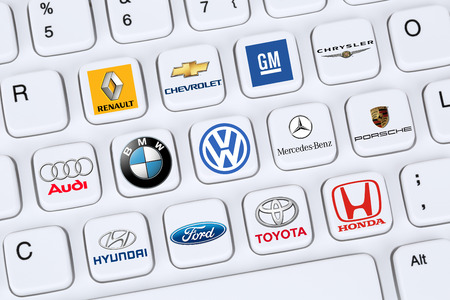 toyota: Berlin, Germany - April 7, 2015: Collection of logos of car companies like Mercedes, GM, VW, Porsche, Ford and Toyota on a computer keyboard.
