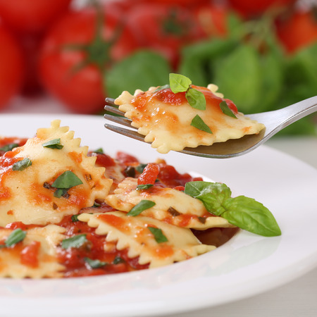 Italian cuisine eating Pasta Ravioli with tomato sauce noodles meal with basil on a plate