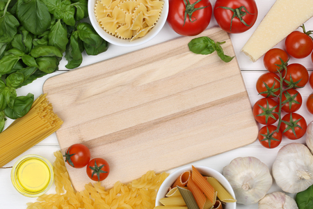 copyspace: Ingredients for a spaghetti pasta noodles meal with tomatoes, Parmesan cheese and copyspace on cutting board