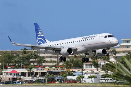 antilles: St. Martin, Netherlands Antilles - February 8, 2014: A Copa Airlines Embraer ERJ190 with the registration HP-1557CMP approaching St. Martin Airport (SXM). St. Martin is rated one of the most dangerous airports in the world. Copa Airlines is the flag carri Editorial