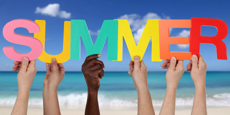 multi racial group: Hands holding the word summer on beach, sand in vacation Stock Photo