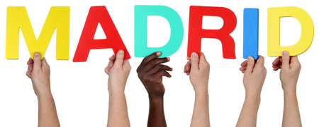multi racial group: Multi ethnic group of people holding the word Madrid isolated Stock Photo