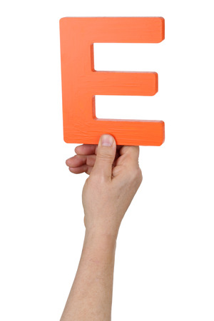 Hand holding letter E from alphabet isolated on a white background photo