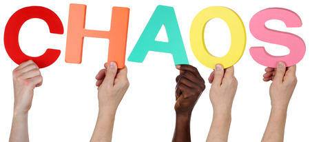 multi racial groups: Multi ethnic group of people holding the word chaos isolated Stock Photo