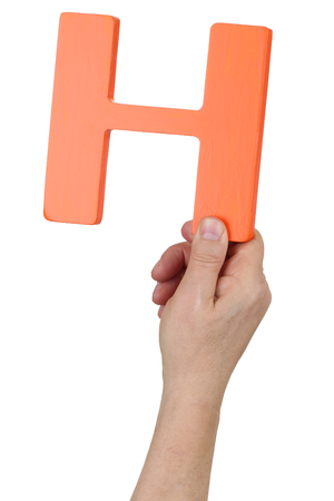 writing a letter: Hand holding letter H from alphabet isolated on a white background