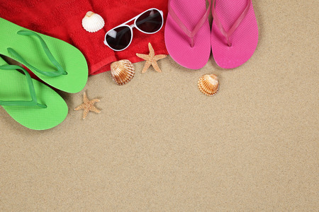 flip flops on the beach: Beach scene in summer on vacation, holiday with sand, sunglasses, towel and copyspace Stock Photo
