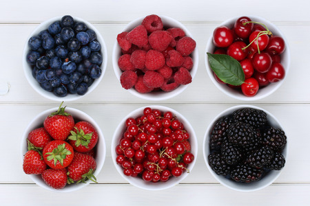 Berry fruits in bowls with strawberries, blueberries, red currants, cherries, raspberries and blackberries Foto de archivo
