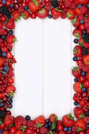 Berries fruits frame with strawberries, blueberries, red currants, raspberries, blackberries and copyspace Banco de Imagens