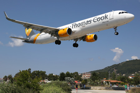 skiathos: Skiathos, Greece - June 23, 2015: A Thomas Cook Airlines Airbus A321 with the registration OY-TCH approaching Skiathos Airport (JSI). Thomas Cook is a charter airline. Skiathos ranks as one of the most dangerous airports in the world.