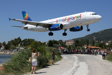 Skiathos, Greece - June 26, 2015: A Small Planet Airlines Airbus A320 with the registration LY-SPA approaching Skiathos Airport (JSI). Small Planet is an airline from Lithuania. Skiathos ranks as one of the most dangerous airports in the world.