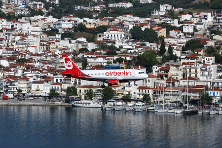 skiathos: Skiathos, Greece - June 28, 2015: An Air Berlin Airbus A319 with the registration OE-LND approaching Skiathos Airport (JSI). Air Berlin is Germanys second biggest airline. Skiathos ranks as one of the most dangerous airports in the world.