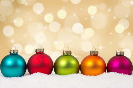 christmas baubles: Colorful Christmas balls in a row golden background decoration with snow and copyspace Stock Photo