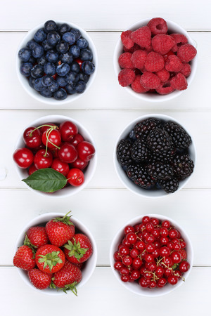 berries: Berry fruits in bowls with strawberries, blueberries, red currants, cherries, raspberries and blackberries from above
