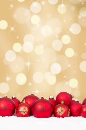 christmas balls: Christmas red balls decoration with golden background, copyspace and snow Stock Photo