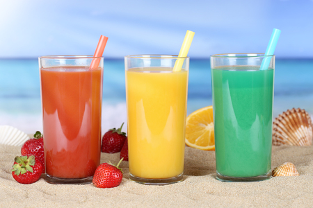 summer fruits: Smoothie fruit orange juice with fruits in summer on the beach