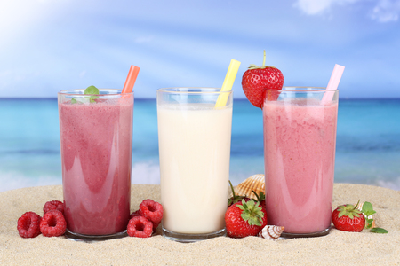 fruit juice: Smoothie fruit juice with fruits in summer on the beach Stock Photo