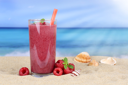 fruit juice: Raspberry smoothie fruit juice cocktail with raspberries fruits in summer on the beach