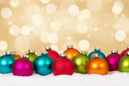 'christmas ball': Christmas card many colorful balls golden background decoration with copyspace and snow