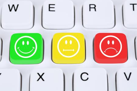 feedback: Choosing customer service quality feedback with smiley on computer keyboard