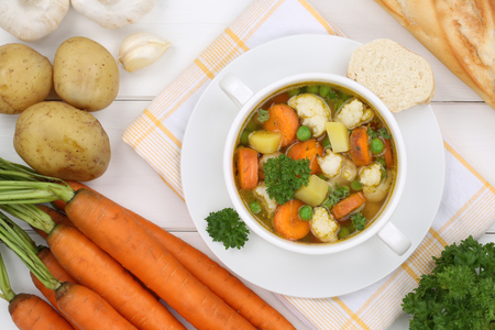 vegetable soup: Vegetable soup meal with vegetables, potatoes, carrots and peas in bowl from above